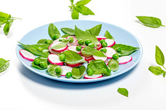 Fresh Basil leaves and radishes on a blue plate