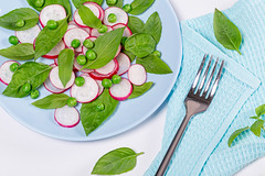 Salad with fresh Basil leaves, radishes and green peas with fork and blue tea towel