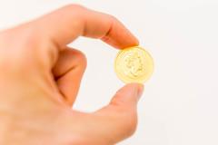 Australische 50 Dollar Münze mit Queen Elizabeth der zweiten in der Hand gehalten auf weißem Hintergrund