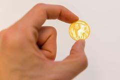 1 Unze Goldmünze Australien Lunar III Maus 2020 in der Hand gehalten auf weißem Hintergrund