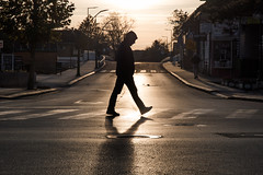 Silhouette of a man crossing the street