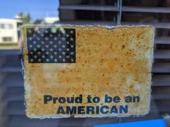 Decaying PROUD TO BE AN AMERICAN sticker, barbershop window, Burbank, California, USA