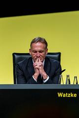 Close-up of the executive Director of German football club BVB, Hans-Joachim Watzke, with thoughtful facial expressions in front of a yellow wall