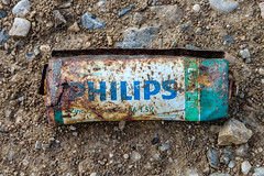 Old and rusty Philips zinc–carbon battery on the ground. Environmental pollution
