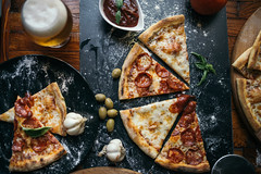 close-up of classic italian Pizza on a old rustic wooden table with beer in glass cups