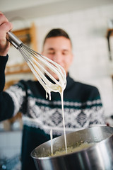 Young man holding bowl with dough and whisk.