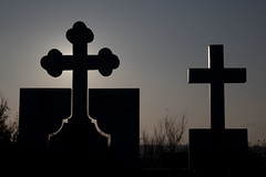 Silhouettes of two crosses at a cemetery