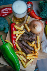 Top view of grilled Serbian sausages with vegetables, french fries and beer.