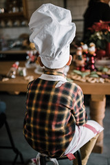 Young boy cook with cap sitting and  ready for cookie baking. Back view portrait.