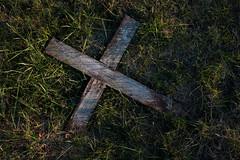 Abgebrochenes Holzkreuz auf einem Friedhof