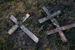 Broken off wooden crosses on the ground at a cemetery