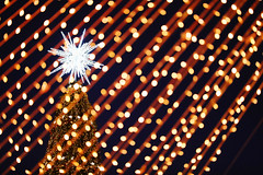 Big star on top of Christmas tree, closeup view through the lights