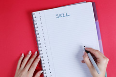 Woman writing Sell text on notebook, red background