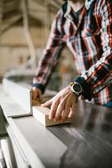 Wood cutting Running circular saw with rotating saw blade. A man works in a workshop