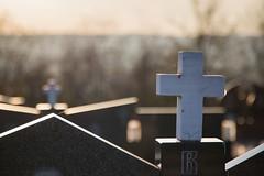 Kreuz aus weißem Granit auf einem Grabstein