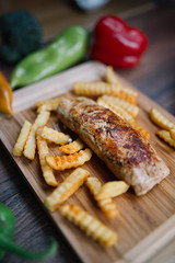 Tasty chicken steak with cheese and french fries on wooden table.