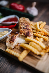 Tasty chicken steak with cheese and french fries on wooden table. Closeup of pickle cheese.