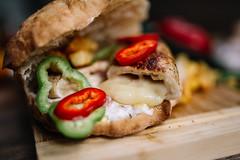 Closeup of grilled stuffed chicken steak in a sandwich.