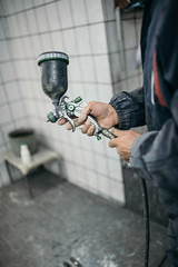 A car-body painter holding an paint spraying gun for painting cars in his paint shop