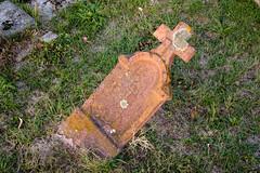 Alter schiefer Grabstein fast auf den Boden gefallen