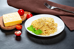 Spaghetti with cheese and sesame seeds on a black background with tomatoes
