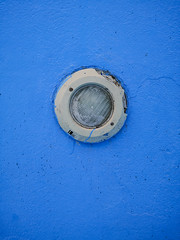Closeup of electric light in swimming pool on blue wall