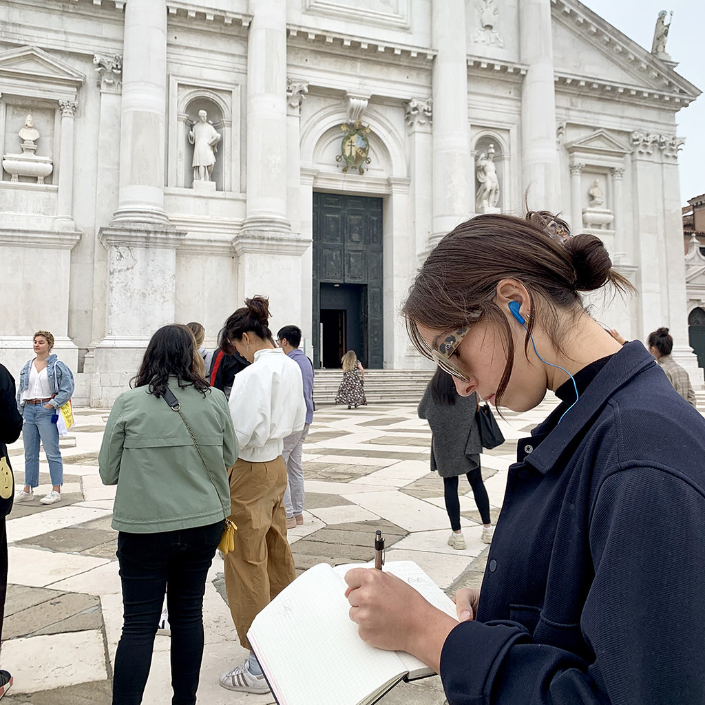 Zeli Grey (B.Arch. '22) draws the exterior of a church and takes notes while listening to Cornell in Rome's Jeffrey Blanchard through her headset during a trip to Venice.   photo / Lauren Peters (B.F.A. '21)