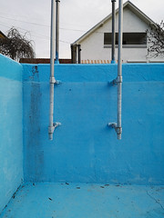 Empty swimming pool in blue color with metal ladder.