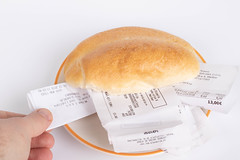 Bread roll full of receipts with human hand
