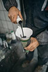 A professional auto painter pouring black color into paint spray gun
