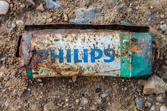 Alte und verrostete Philips Zink-Kohle Batterie auf dem Boden. Umweltverschmutzung