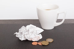 Coffee cup with receipt and coins on table