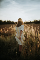 A girl in a white glamour dress going alone in a meadow and relaxes.