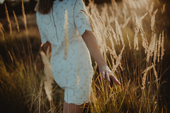 A girl in a white dress going alone in a meadow and relaxes.  Closeup of woman`s arm in nature