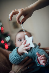 Baby girl grabs and catches toy star.  Beautiful baby in a blue swater in the interior with Christmas decorations.
