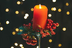 A red candle burns on a dark background with bokeh