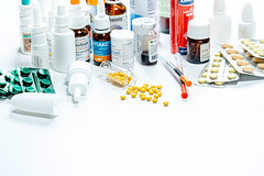 Composition of medicine bottles and pills on white background