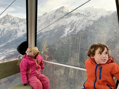 The twins crane their necks to see the 360 degree delights of the Alps in our gondola