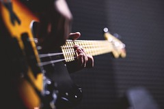 Person playing sun burst electric bass guitar in bokeh - Credit to https://homegets.com/
