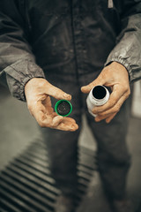 A professional auto painter holding paint for car paintjob in his hands