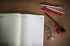 Notebook, pencil and glasses on desk at home