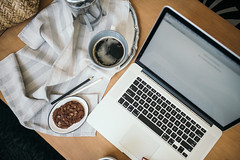 Worksplace of stylish glamour woman. Coffee, cookie and macbook at home.