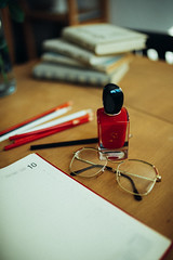 Notebook, pencil, glasses and red nail polish on desk at home