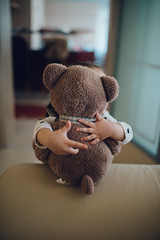 Little girl hugs teddy bear toy