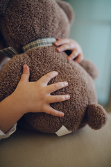 Little girl hugs teddy bear. Closeup arms.