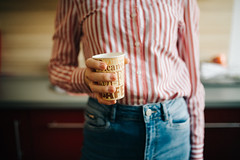 woman in striped shirt holding paper cup of coffee standing in kitchen near stove. Morning concept. Ready for work.