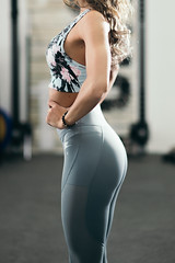 Sexy sportswoman standing and concentrating in gym in the middle of the workout