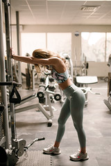 Young attractive woman relax at gym standing by fitness machine