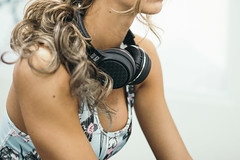 Young handsome girl listening to music at the gym. Headphones closeup.