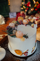 Christmas beautiful cake with fruits. Snow fall.
